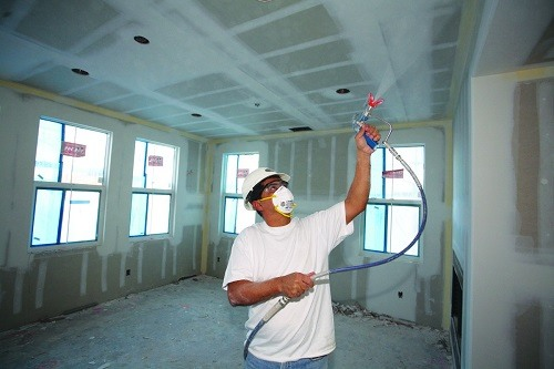 Man using an airless paint sprayer.