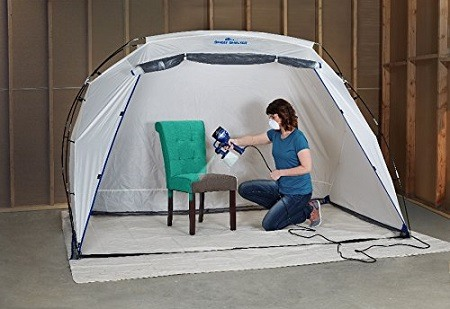 Woman using HomeRight C800766 Finish Max Fine Finish Sprayer in a tent as a cover.