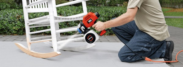 Man using a paint sprayer on a chair.