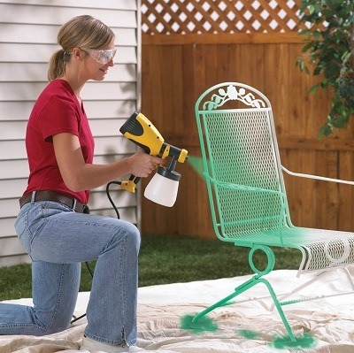 Woman using Wagner 0417005 Control Spray HVLP Sprayer on a chair.